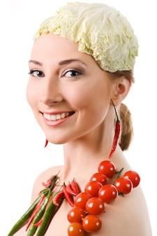 Portret van vrolijk europees meisje met rode en groene paprika's, kerstomaatjes op lichaam en koolblad op hoofd