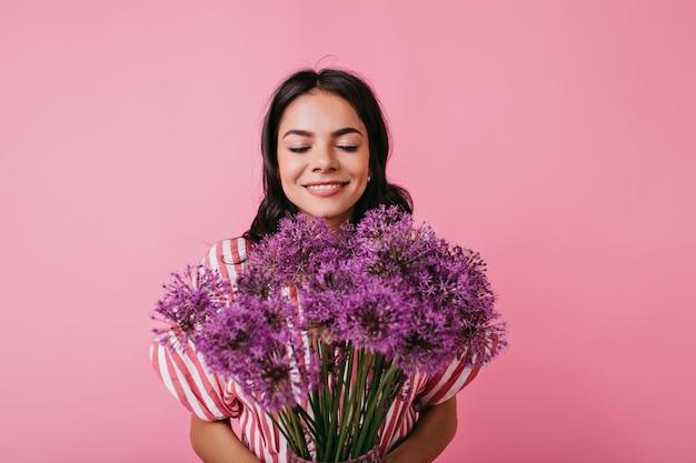 Portret van vrolijk gelukkig meisje dat van geur van bloemen geniet. leuke dame met mooi bruin plezier