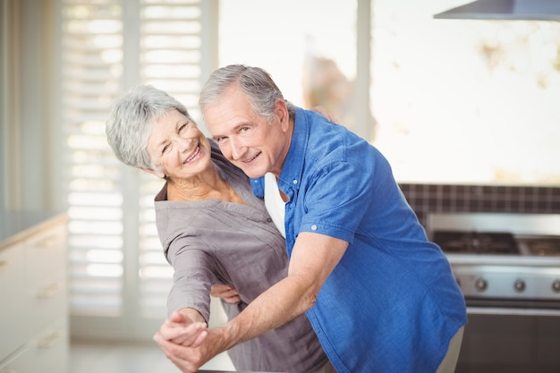 Portret van vrolijk hoger paar dat in keuken danst