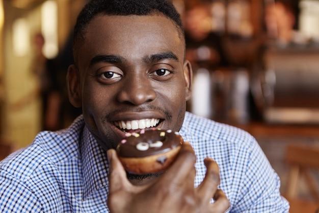 Portret van vrolijk jong afrikaans mannetje dat formeel geruit overhemd draagt dat geglazuurde doughnut houdt