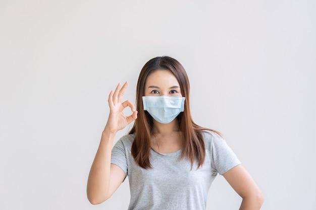 Portret van vrolijk jong aziatisch meisje met beschermend gezichtsmasker dat boete in gebarentaalhand toont