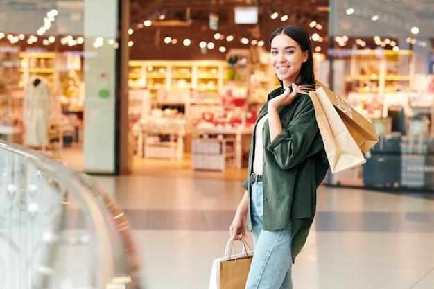 Portret van vrolijk jong meisje in groen overhemd bevindende papieren zakken met aankopen in winkelcentrum
