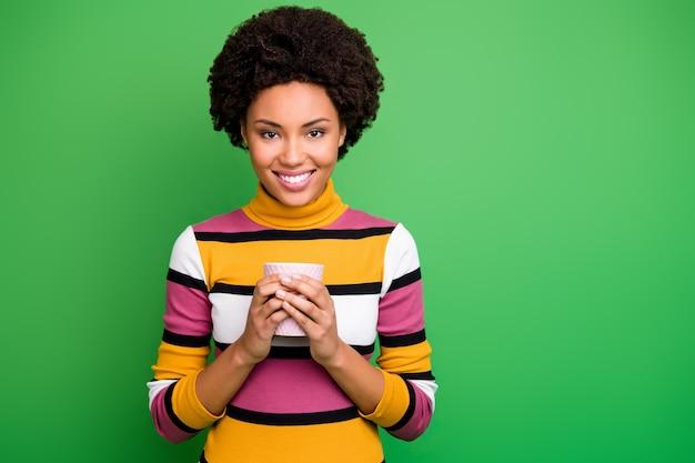 Portret van vrolijk kalm afro-amerikaans meisje houdt hete cafeïne drank beker geniet van herfstweekends draag goede kleding