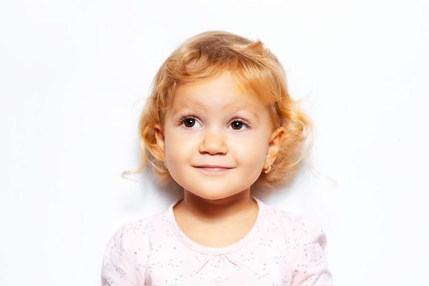 Portret van vrolijk kindmeisje met krullend blond haar, dat omhoog kijkt