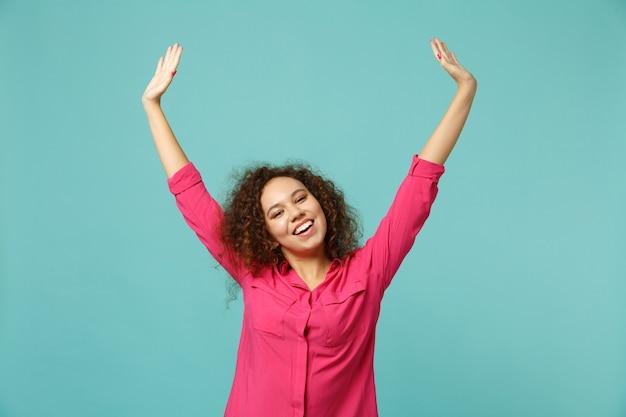 Portret van vrolijk lachend aantrekkelijk afrikaans meisje in casual kleding stijgende handen geïsoleerd op blauwe turquoise muur achtergrond in studio. mensen oprechte emoties, lifestyle concept. bespotten kopie ruimte.