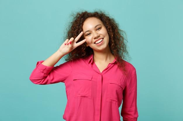Portret van vrolijk lachend afrikaans meisje in casual kleding met overwinningsteken geïsoleerd op blauwe turquoise muur achtergrond in studio. mensen oprechte emoties, lifestyle concept. bespotten kopie ruimte.
