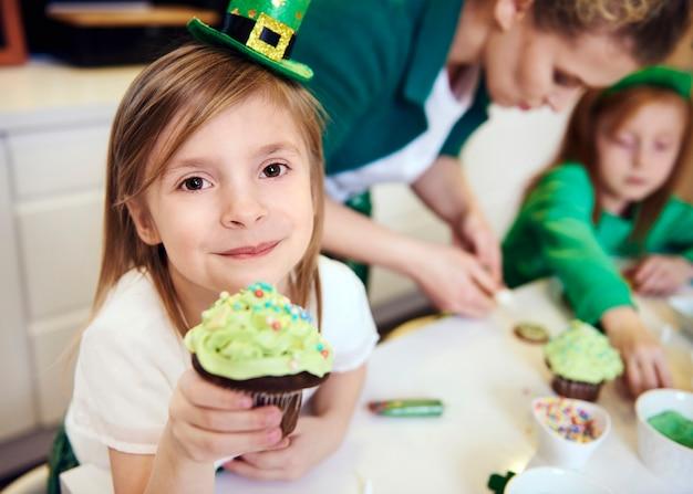 Portret van vrolijk meisje dat cupcake toont
