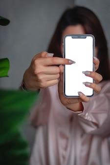 Portret van vrolijk meisje wijzend op mobiele gadget met kopieerruimte voor internetreclame, gelukkige vrouwelijke millennial met smartphone met leeg scherm