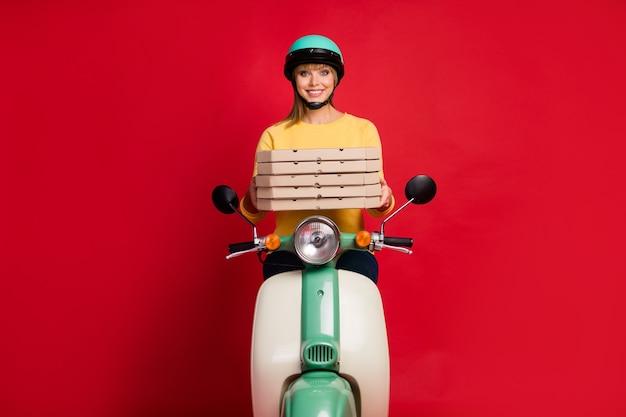 Portret van vrolijk meisje zittend op bromfiets bedrijf in handen stapel stapel stapel pizza
