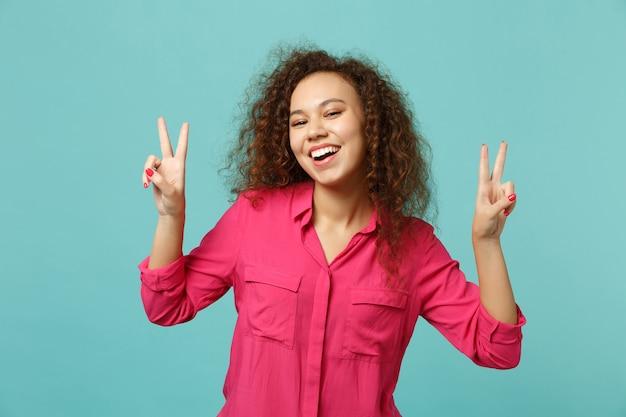 Portret van vrolijk mooi afrikaans meisje in casual kleding met overwinningsteken geïsoleerd op blauwe turquoise muur achtergrond in studio. mensen oprechte emoties, lifestyle concept. bespotten kopie ruimte.
