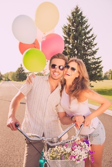 Portret van vrolijk mooi paar verliefd op fietsen en ballonnen