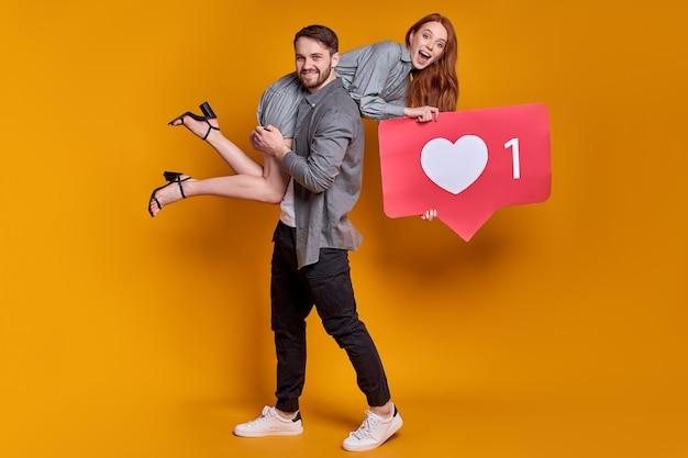 Portret van vrolijk paar in feestkleding met hart als pictogram, dat aanbeveelt om op de knop voor sociale media te klikken die op een oranje muur wordt geïsoleerd