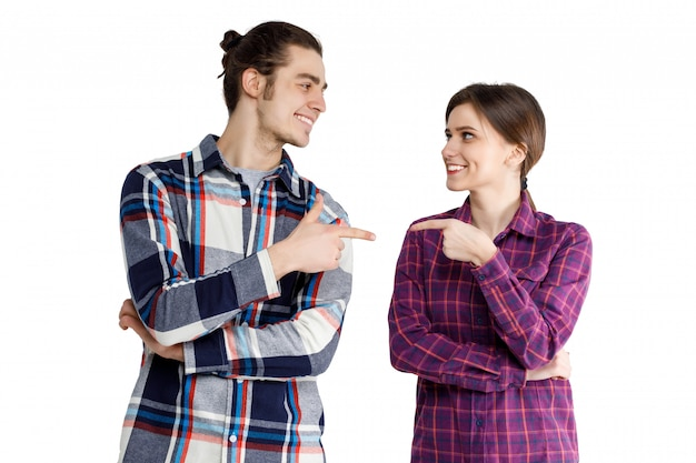 Portret van vrolijk positief en leuk paar in denimt-shirt die en aan elkaar glimlachen richten