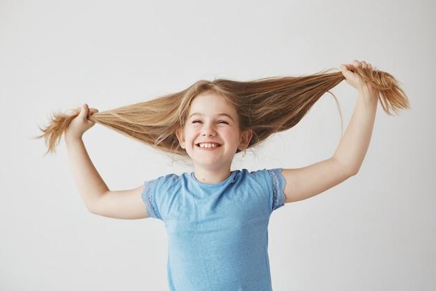 Portret van vrolijk schattig klein blond meisje in blauw t-shirt lachen met gesloten ogen, met haar met handen, met plezier.