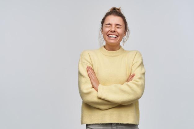 Portret van vrolijk, volwassen meisje met blond haar dat in broodje wordt verzameld. gele trui dragen. lachend met gesloten ogen en gekruiste armen op de borst. tribune geïsoleerd over witte muur
