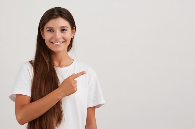 Portret van vrolijk, volwassen meisje met donker lang haar, gekleed in een wit t-shirt