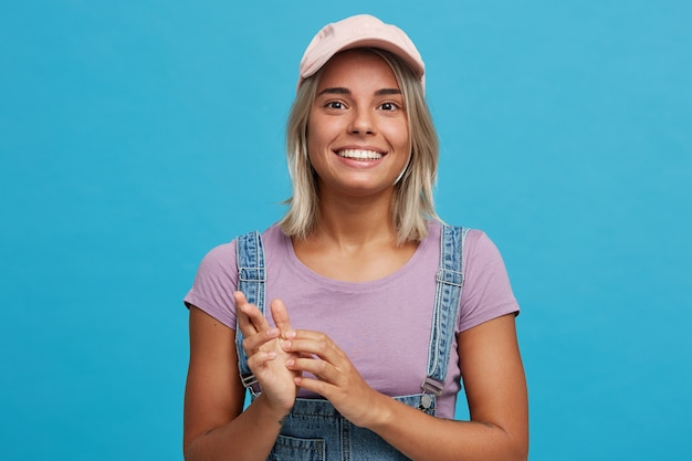 Portret van vrolijke aantrekkelijke blonde jonge vrouw draagt roze pet, violet t-shirt en denim overall voelt zich gelukkig en glimlachend geïsoleerd over blauwe muur