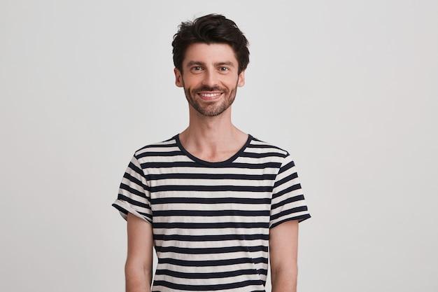 Portret van vrolijke aantrekkelijke jonge man met borstelharen draagt een gestreepte t-shirt voelt zich gelukkig, staand en glimlachend geïsoleerd over witte muur kijkt naar voren