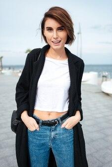 Portret van vrolijke aantrekkelijke jonge vrouw die buiten loopt