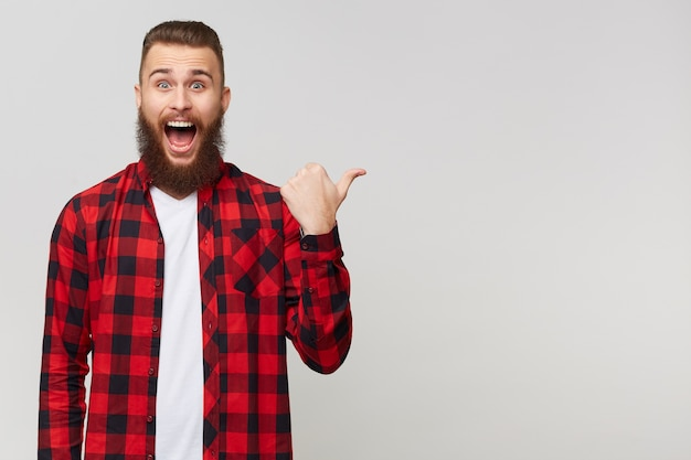 Portret van vrolijke aantrekkelijke vrolijke bebaarde man in geruit overhemd met snor mode kapsel, mond geopend vanwege verbazing wijzend op copyspace achter zijn rug geïsoleerd op witte muur