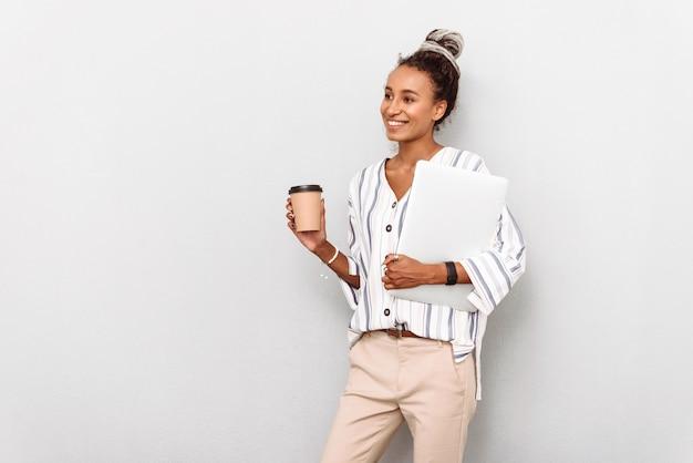 Portret van vrolijke afrikaanse zakenvrouw met dreadlocks op wit wordt geïsoleerd drinken koffie met laptopcomputer.