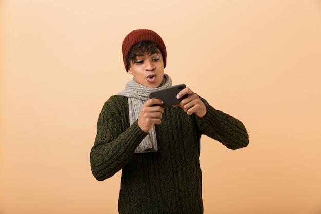 Portret van vrolijke afro-amerikaanse gamerjongen die hoed en sjaal draagt die videospelletjes op smartphone speelt, die over gele muur wordt geïsoleerd