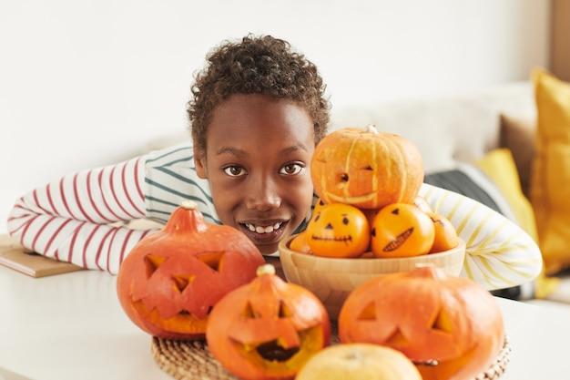 Portret van vrolijke afro-amerikaanse jongen die zich voordeed op camera met pompoenen en mandarijnen die hij op halloween voorbereidde