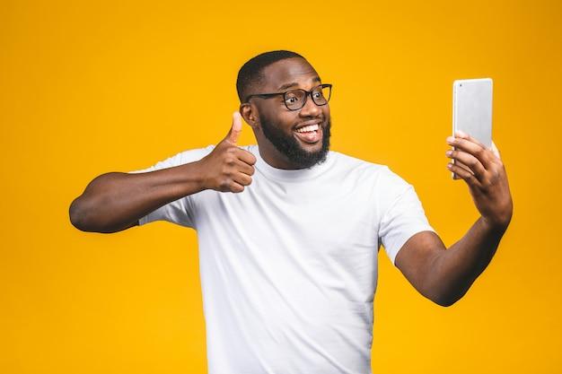 Portret van vrolijke afro-amerikaanse man op vakantie, geïsoleerd op gele muur, in vrijetijdskleding, met behulp van veb cam op zijn tablet, genieten, glimlachend. duimen omhoog.