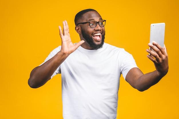 Portret van vrolijke afro-amerikaanse man op vakantie, geïsoleerd op gele muur, in vrijetijdskleding, met behulp van veb cam op zijn tablet, genieten, glimlachend.