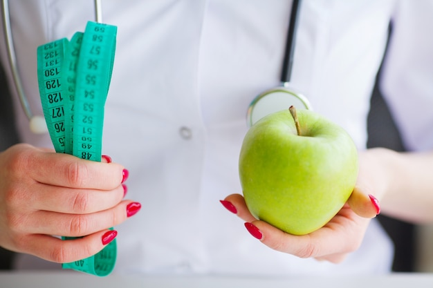 Portret van vrolijke artsenvoedingsdeskundige die groene appel in haar bureau meten