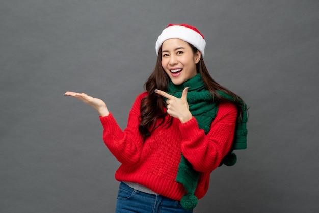 Portret van vrolijke aziatische vrouw die kerstmiskledij met open palmgebaar draagt