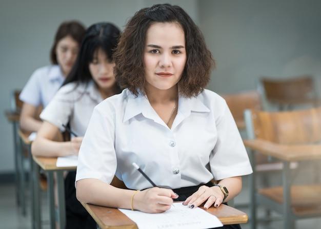 Portret van vrolijke aziatische vrouwelijke studenten die schrijven en studeren in de klas. selectieve vier tieneruniversiteitsstudenten die in klaslokaal studeren.