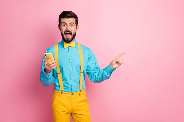 Portret van vrolijke bebaarde kerel die in handencel houdt die exemplaarruimte toont