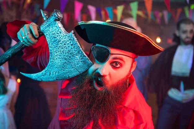 Portret van vrolijke bebaarde mannen verkleed als een piraat op een halloween-feestje. man in een dracula-kostuum op de achtergrond.