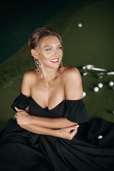 Portret van vrolijke blanke dame glimlacht, foto geïsoleerd op donkere wazige achtergrond