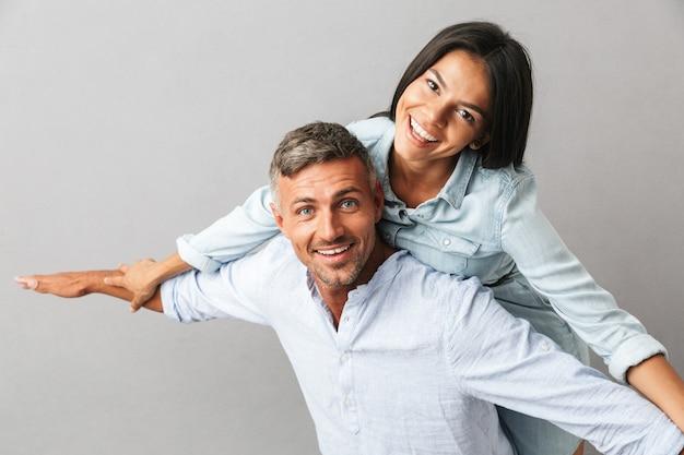 Portret van vrolijke blanke mensen man en vrouw in basic kleding glimlachen en knuffelen samen, geïsoleerd over grijs