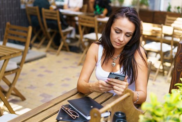 Portret van vrolijke blanke vrouw die naar straat kijkt terwijl ze in café zit met mobiele telefoon en n...
