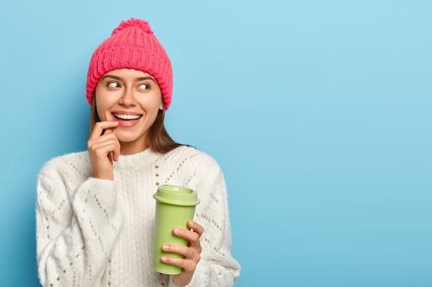 Portret van vrolijke blanke vrouw houdt vinger op lip, drinkt afhaalmaaltijden koffie, houdt groenboek beker, gekleed in warme witte trui, opzij gericht