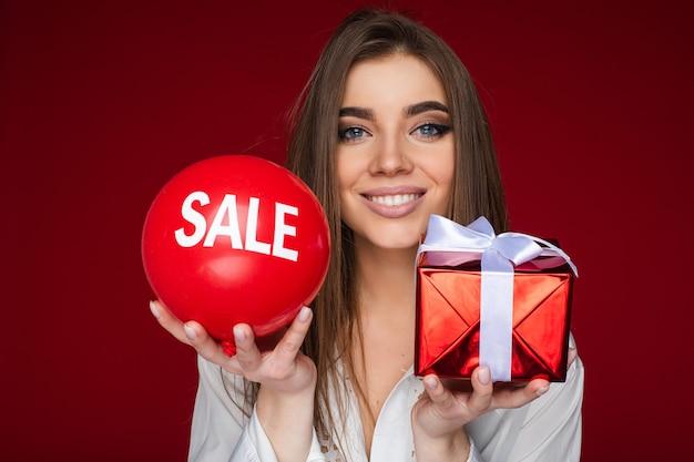 Portret van vrolijke blanke vrouw met rode ballon met verkoop erop enerzijds en rode doos met een geschenk anderzijds