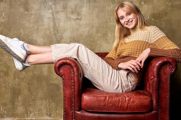 Portret van vrolijke blanke vrouw zittend op een leren bank