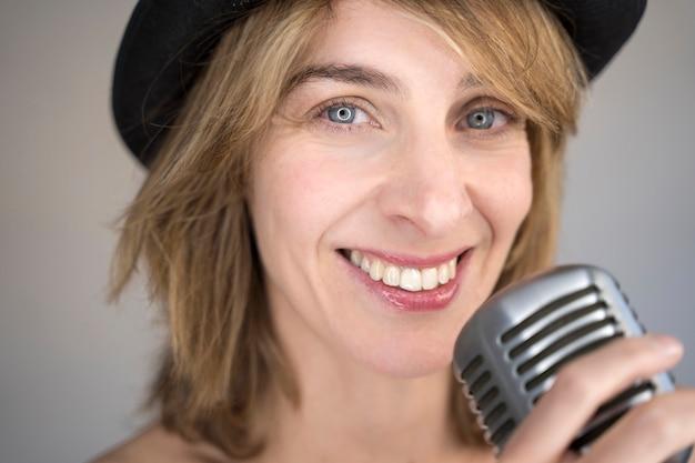 Portret van vrolijke blonde vrouw die een lied met een uitstekende zilveren microfoon zingt. muziekapparatuur en muzikale carrière concept.