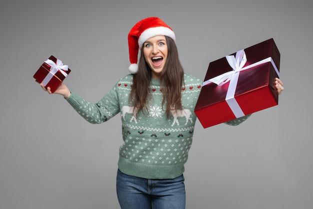 Portret van vrolijke brunette in groene trui met winterpatroon en rode kerstmuts met twee cadeautjes van verschillende grootte in rood papier met open mond..