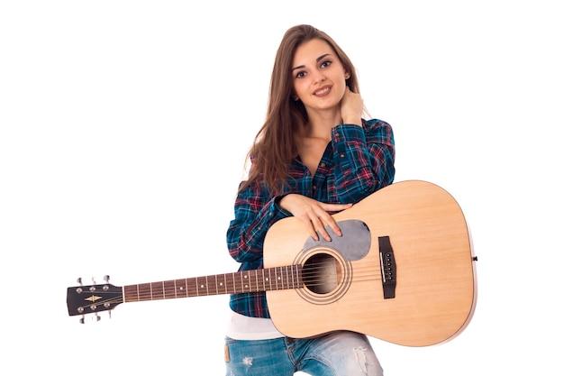 Portret van vrolijke brunette meisje gitaar spelen geïsoleerd op een witte achtergrond