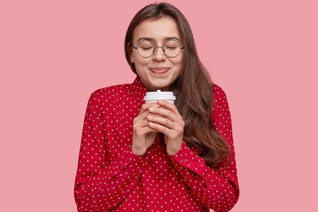 Portret van vrolijke brunette vrouw met gesloten ogen, houdt afhaalmaaltijden koffie, verwarmt handen, heeft een romantische uitdrukking