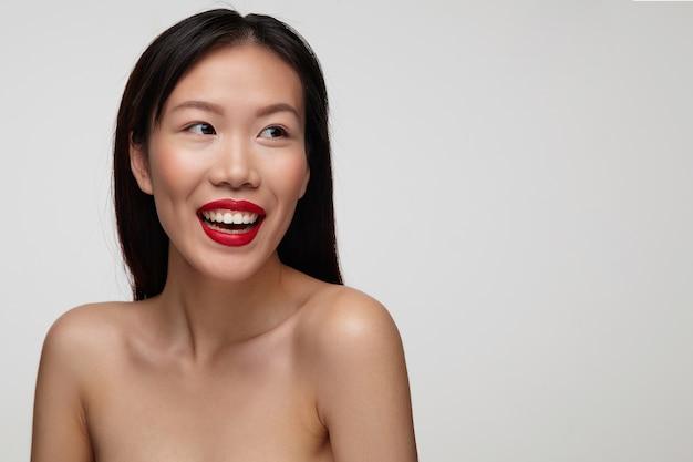 Portret van vrolijke charmante donkerharige jongedame met rode lippen breed glimlachend terwijl ze vreugdevol opzij kijkt, staande over witte muur met blote schouders