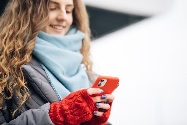 Portret van vrolijke curly-haired jonge vrouwelijke texting op smartphone staande op straat in winter stad op nieuwjaar.
