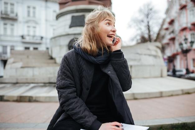Portret van vrolijke dame met blond haar die op haar cellphone spreekt terwijl vreugdevol opzij op stadsstraat kijkt