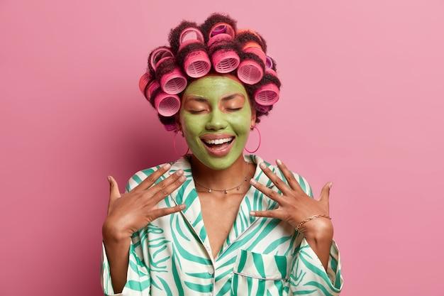 Portret van vrolijke dame met groen schoonheidsmasker voor een gezonde huid, houdt de ogen gesloten, droomt over fantastische kijk op feestje, maakt perfecte kapsel, gekleed in huiselijk gewaad geïsoleerd op roze