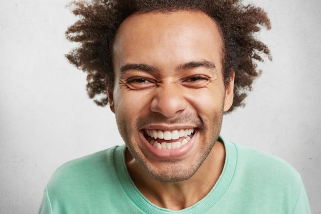 Portret van vrolijke dolgelukkig man met borstelige kapsel, glimlacht gelukkig,