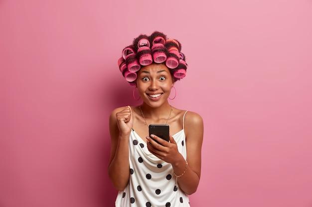 Portret van vrolijke donkere vrouw leest uitstekend nieuws op smartphone, werpt gebalde vuist en glimlacht tootily, past haarkrulspelden toe voor kapsel. huisvrouw maakt thuis gebruik van sociale netwerken